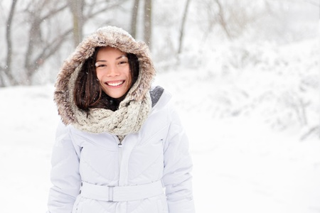 Snow winter woman portrait outdoors on snowy white winter day. Beautiful asian girl smiling happy outside. photo