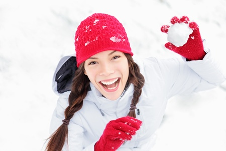 winter day: winter girl throwing snowball at camera smiling happy having fun outdoors on snowing winter day playing in snow. Cute playful multicultural Asian Caucasian young woman outdoor enjoying first snow.