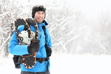 outdoorsman: Winter snowshoeing. Young outdoorsman hiker standing smiling happy holding snowshoes outside in the snow during snowshoe hiking trip. From Quebec, Canada.