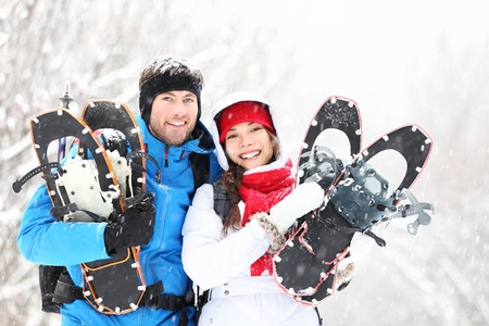 snowshoeing: Winter couple happy outdoor hiking in snow on snowshoes. Healthy lifestyle photo of young smiling active mixed race couple snowshoeing outdoors. Asian woman, caucasian man.