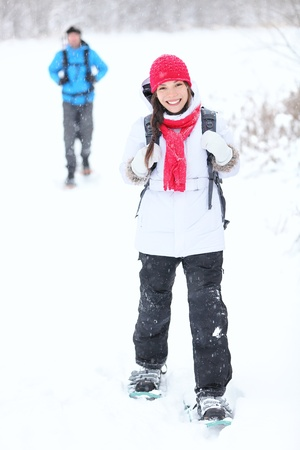 snowshoeing: snowshoeing winter hiking. Active couple on snowshoes outdoors in snow walking in natural park in Canada, Quebec.
