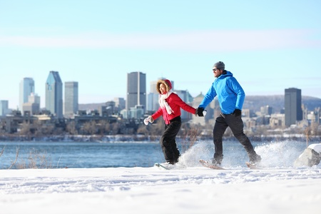 Winter fun couple on snowshoes running with montreal cityscape skyline and river st. Lawrence in background. Healthy lifestyle photo from Montreal, Quebec, Canada.