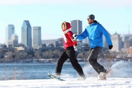 snowshoeing: Happy couple snowshoeing running in montreal with cityscape skyline and river st. Lawrence in background. Healthy lifestyle photo from Montreal, Quebec, Canada.