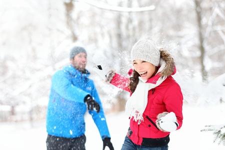boule de neige: Snowball Fight. Quelques hiver en s'amusant à jouer dans la neige à l'extérieur. Jeunes joyeuse heureuse multi-racial couple.