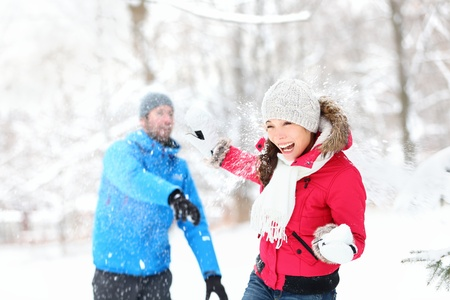 couple fight: Snowball fight. Winter couple having fun playing in snow outdoors. Young joyful happy multi-racial couple.