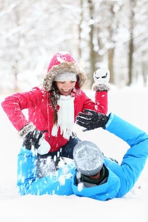 bolas de nieve: Invierno lucha par de bolas de nieve. Pareja de j�venes se divierten en la nieve fuera. pareja de j�venes en sus veintes.