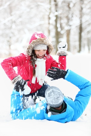 snowballs: Winter couple snowball fight. Young couple having fun in snow outside. young couple in their twenties. Stock Photo