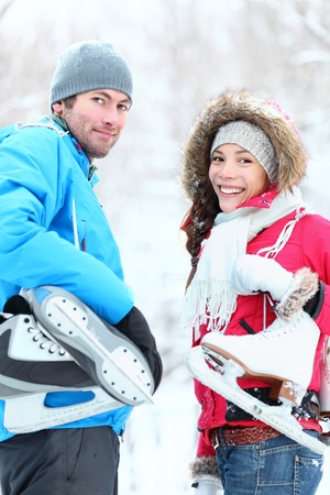 skaters: Ice skating winter couple smiling happy holding ice skates outdoors. Beautiful young couple, Asian woman, Caucasian man outside on snow winter day. Stock Photo