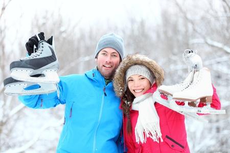 patinaje sobre hielo: El hielo de patinaje en invierno pareja sonriendo feliz y emocionado mostrando los patines de hielo al aire libre en la nieve. Hermosa joven pareja multirracial concepto de estilo de vida saludable. Foto de archivo