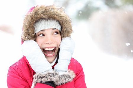 Excited winter woman looking to side smiling happy and joyful holding head. Beautiful mixed race asian cauasian girl playful in the snow. photo