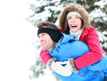 Winter couple piggyback in snow smiling happy and excited. Beautiful young multiracial couple, Asian woman, Caucasian man piggybacking photo