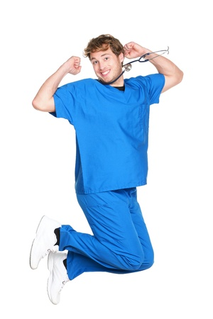 happy people jumping: happy male nurse or doctor jumping in blue scrubs smiling excited. Young medical professional. Caucasian man in his twenties wearing stethoscope isolated on white background.