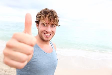 hombre deportista: El hombre joven los pulgares arriba. Sonriente hombre feliz deportivo dando pulgares en se�al de �xito a la c�mara durante el entrenamiento al aire libre en la playa. Hermoso modelo de fitness masculino de unos 20 a�os. Foto de archivo