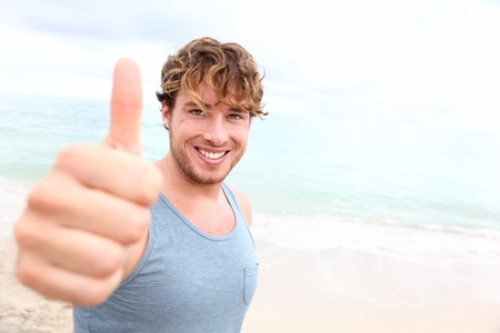 male's thumb: Young man thumbs up. Smiling happy sporty man giving thumbs up success sign to camera during training outside on beach. Handsome male fitness model in his 20s.