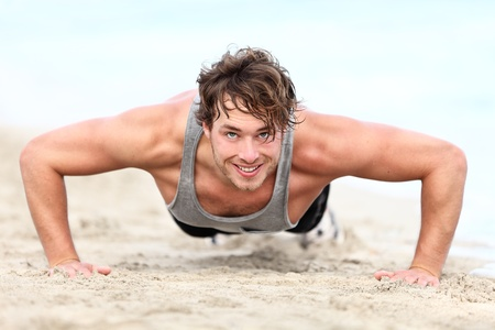 pushup: fitness man exercising push ups smiling happy. Male fitness model cross-training on beach. Caucasian man in his twenties. Stock Photo