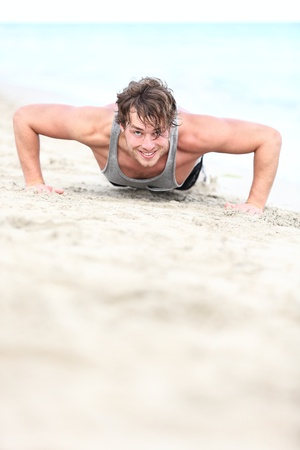 pushups: sport man training push ups on beach. Young hand some caucasian fitness model in his twenties working out outside on beach. Stock Photo