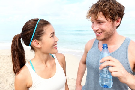 Fitness couple on beach talking relaxing and smiling happy after running training. Multiracial couple: Asian woman and Caucasian man drinking water photo