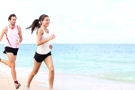 sport - couple running on beach traing for marathon run. Young multiracial couple runners, smiling asian female fitness model and caucasian male model.