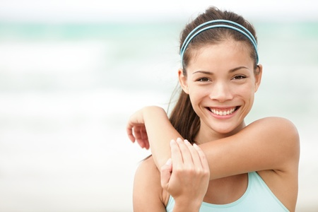 stretching: Fitness woman exercising smiling happy stretching out doing workout on beach. Beautiful mixed race Asian Caucasian female fitness model portrait. Stock Photo