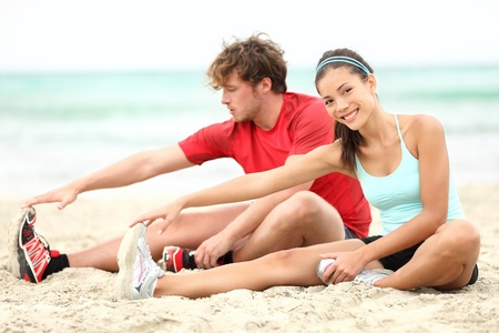 Couple training on beach stretching legs after running. Young man and woman during summer workout. Asian female fitness model, Caucasian male fitness model. Stock Photo