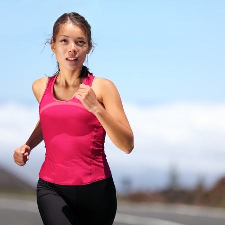 fitness model: runner - woman running outdoors training for marathon run. Beautiful fit asian fitness model in her 20s.