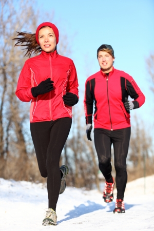 Sport couple running in winter snow. Woman and man runners jogging outdoors. Healthy fitness lifestyle concept with happy smiling young multiracial couple. photo