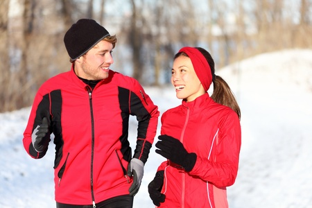 Couple running in winter snow living healthy lifestyle. Man and woman runner in their 20s. Young multi-ethnic couple, Asian woman, Caucasian man. photo