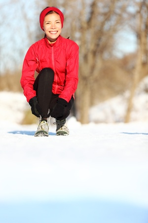 Winter runner getting ready running tying shoe laces. Beautiful young mixed race Asian  Caucasian female fitness model training outside. Copy space on snow. photo