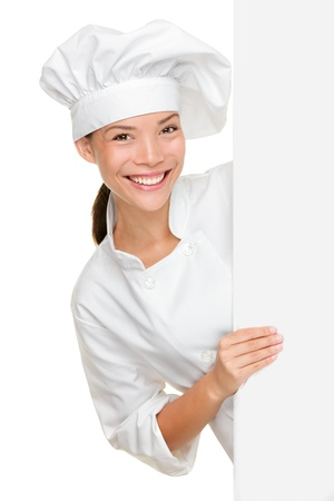 Chef showing blank sign. Woman chef, baker or cook smiling happy holding blank white paper sign isolated on white background. Beautiful young mixed race Asian Caucasian female model.