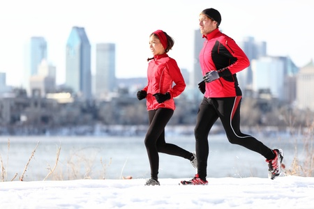 Runners running in winter snow with city skyline background. Healthy multiracial young couple. Asian woman runner and Caucasian man running with Montreal skyline, Quebec, Canada photo