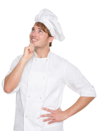 chefs whites: Thinking chef, baker or male cook. Young man in chefs whites uniform smiling happy looking up. Portrait of young chef in his twenties.