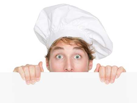 Chef sign. Man chef, cook or baker peeking up holding blank white paper sign with copy space for text or menu. Young Caucasian male chef looking funny surprised isolated on white background. photo
