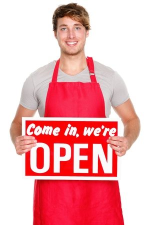 business owner: Business owner  employee showing open sign. Man wearing red apron smiling happy. Caucasian male model. Stock Photo