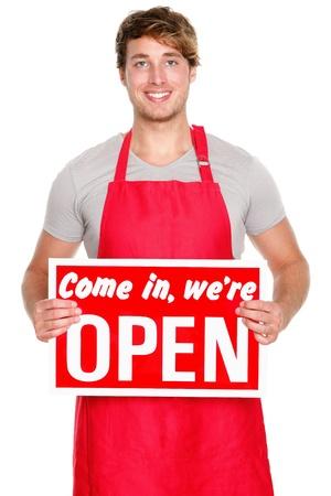 oficinista: Propietario de una empresa  empleado que muestra señal abierta. Hombre con delantal rojo sonriendo feliz. Caucásica modelo masculino.