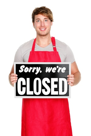 Business owner  employee showing closes sign. Man wearing red apron smiling happy. Caucasian male model. photo