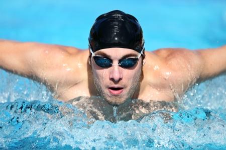 natacion: Nadador. El hombre de natación carreras de mariposa en la competencia. Nadador competitivo deporte masculino llevaba gafas de natación y la tapa. Joven, caucásico modelo de fitness masculino.