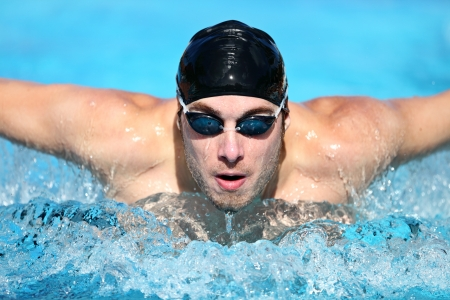 swimming race: Swimmer. Man swimming butterfly strokes in competition. Competitive male sport swimmer wearing swimming goggles and cap. Young caucasian male fitness model.