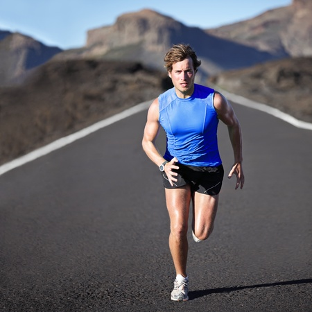 road runner: Sport man running. Runner sprinting training for marathon. Young strong male fitness model during run outdoors in beautiful landscape.
