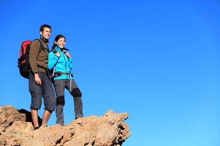 Hikers looking at view. Hiking young couple enjoying view looking at blue sky during hike. Multiracial couple with a lot of copy space. photo