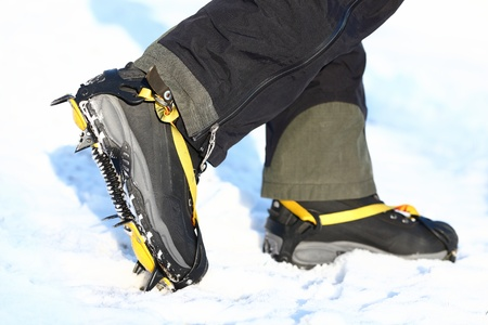crampons: Crampons and shoes walking on ice and snow during outdoor winter trekking. Close up. Stock Photo