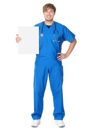 Male doctor  nurse showing billboard sign. Young medical professional wearing blue scrubs and stethoscope standing in full body isolated on white background. photo