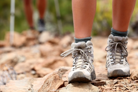 walking boots: Hiking shoes close up outoors during hike - female shoes. Hikers in the background