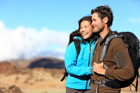 woman hiking: Hiking couple looking at view smiling happy. Young beautiful multiracial couple hikers in their twenties on hike.