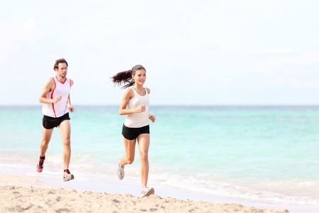 Couple running on beach. Runners jogging outside training. Caucasian  Asian woman runner and Caucasian fitness man model. photo