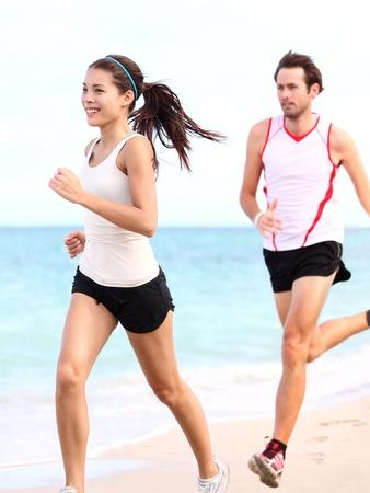 ジョグ: 実行している人々: ランナーのビーチに屋外トレーニングのカップルします。若い多民族女性フィットネス モデルと白人男性ランナー。