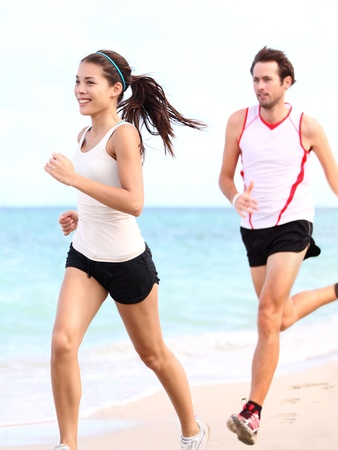 People running: couple runners training outdoors on beach. Young multiracial woman fitness model and caucasian man runner.