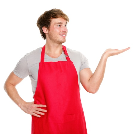 Apron man showing. Small business shop owner showing and looking wearing red apron. Happy smiling and proud caucasian man presenting isolated on white background. photo