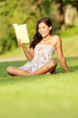 Woman reading book in spring  early summer. Cute student girl in sundress sitting in grass in park reading book smiling happy. Beautiful multiracial Asian  Caucasian female model. photo
