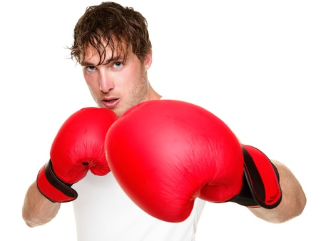 agressive: Fitness boxer boxing. Man punching with red boxing gloves isolated on white background. Fit fitness boxer sweating looking at camera. Caucasian male fitness model in his 20s.