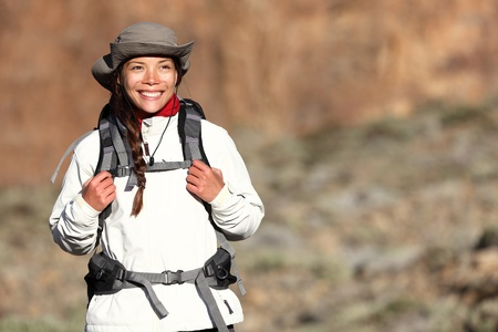 Hiking - woman hiker walking outdoors in mountain landscape smiling happy looking at copy space. Multiracial Asian Caucasian female model outdoors. photo